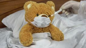 A teddy bear measures the temperature with a mercury thermometer. The doctor puts a thermometer to the bear. The bear