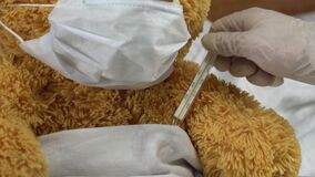 A teddy bear measures the temperature with a mercury thermometer. The doctor takes the thermometer closeup. The bear