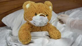 A teddy bear measures the temperature with a mercury thermometer. The doctor takes the thermometer. The bear lies in bed