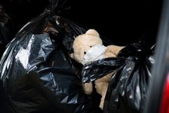 A teddy bear with a medical bandage on his face lies on the waste bags