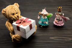 Teddy bear and mini angel. Valentine background. Decoration of brown teddy bear holding gift box and mini angel doll carrying pink flower on old black textured Stock Photo