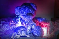 Teddy Bear mit dekorativen Lichtern und Stern beleuchtet im Bett stockbild