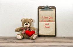Teddy Bear mit rotem Herzen und Klemmbrett Roter heart-shaped Schmucksachegeschenkkasten und eine rote Spule auf einem Zeichen Stockfotografie