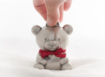 Teddy bear money box. Depositing a coin into a child's teddy bear money box Royalty Free Stock Images