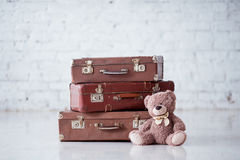 Teddy bear near stack of three brown retro suitcases on white floor Royalty Free Stock Photography