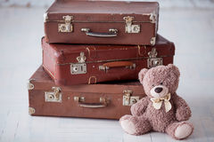 Teddy bear near stack of three brown retro suitcases on white floor Stock Images
