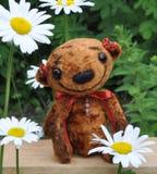 Teddy-bear Niusia. Handmade, the sewed plush toy: Teddy-bear Niusia weirdo on a board among flowers Stock Photos
