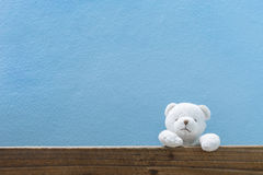 Teddy bear on old wood and blue wall background. Royalty Free Stock Photos