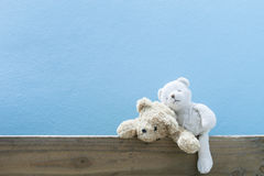 Teddy bear on old wood blue wall background. Royalty Free Stock Photo