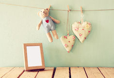 Teddy bear over wood table next to photo frame and fabric hearts. retro filtered image Royalty Free Stock Photography