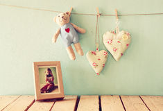 Teddy bear over wood table next to photo frame with kid's old photography and fabric hearts. retro filtered image Stock Image