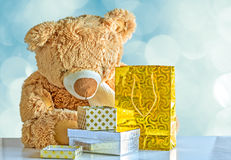 Teddy bear and packages with gifts Stock Images