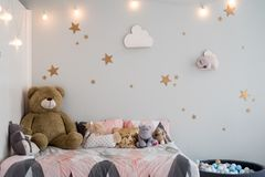Teddy bear between paper bags and wooden chairs in child's room with pastel lamp above table royalty free stock photos