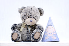 Teddy bear and party hat Stock Images