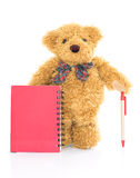 Teddy bear with pen and blank red notebook Stock Photos