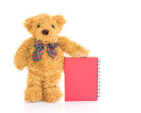 Teddy bear with pen and blank red notebook Royalty Free Stock Photo