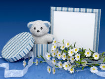 Teddy bear with a photo frame and flowers Stock Photography