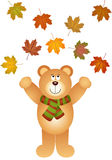 Teddy bear picking up fall leaves Stock Photo
