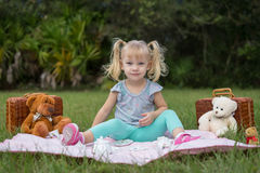 Teddy Bear Picnic. A sweet little girl in pigtails enjoying a picnic with her teddy bear friends stock images