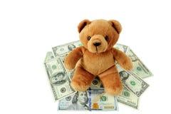 Teddy Bear on the pile of US dallar. Stock Photos