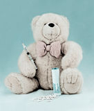 Teddy bear with pills and syringe Stock Images