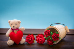 Teddy bear with pink heart decoration on wooden table over wall Royalty Free Stock Photography