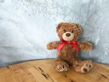 Teddy bear is placed on a wooden table. Concrete backdrop Can be used for display or montage your production. Presentation of advertising ideas stock images
