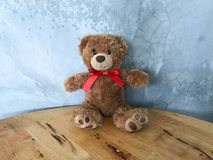 Teddy bear is placed on a wooden table. Concrete backdrop Can be used for display or montage your production. Presentation of advertising ideas stock image