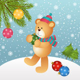 Teddy bear placing glass balls in Christmas tree Royalty Free Stock Image