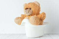 A teddy bear in a potty next to stack of diapers Stock Photo