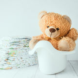 A teddy bear in a potty next to stack of diapers stock image