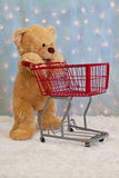 Teddy bear pushing red shopping cart Stock Image