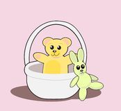 Teddy Bear and Rabbit. A teddy bear sitting in a basket and a green toy rabbit Royalty Free Stock Photo
