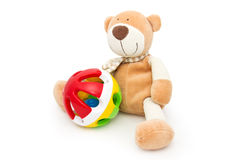 Teddy bear with a rattle. Children's toys: brown teddy bear and colorful rattle Stock Photography