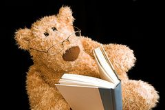 Teddy bear reading. Teddy bear with glasses reading a book by himself Royalty Free Stock Image