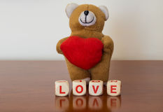Teddy bear with red heart and love word Royalty Free Stock Image