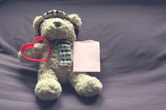 Teddy bear with red heart shape and empty note paper on bed. Stock Photos