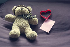 Teddy bear with red heart shape and empty note paper on bed. Stock Image