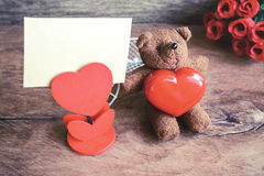 Teddy bear with red heart shape and notebook on old wooden backg Royalty Free Stock Photos