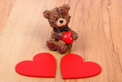 Teddy bear with red heart on wooden surface, symbol of love Stock Photography