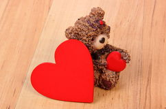 Teddy bear with red heart on wooden surface, symbol of love Royalty Free Stock Image