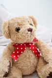 Teddy bear with red polka dot ribbon. Teddy bear sitting with a red polka dot ribbon Royalty Free Stock Images