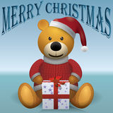 Teddy bear in red sweater red hat with present text MerryChristmas.  Stock Image