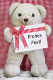 Teddy bear with a red and white checkered greeting card for chri Stock Photography