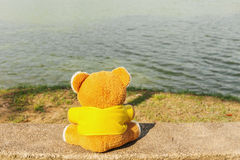Teddy bear relax on the chair with riverside Royalty Free Stock Photo