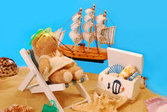 Teddy bear relaxing on the beach Stock Images