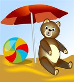 Teddy bear with resting on the sea under the red umbrella Stock Images