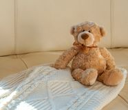 Teddy Bear with ribbon sitting on cozy knitted white Christmas sweater on beige leather sofa background. Warm comfortable winter stock image