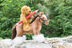 Teddy bear ride a horse in forest Royalty Free Stock Image