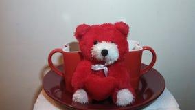 Teddy Bear rojo y blanco con dos tazas y una placa Imagen de archivo libre de regalías